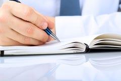 Écriture d'homme d'affaires dans un carnet tout en se reposant à un son bureau Photographie stock libre de droits