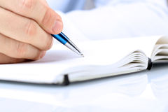 Écriture d'homme d'affaires dans un carnet tout en se reposant à un son bureau Photo stock