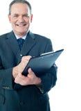 Écriture d'homme d'affaires sur la planchette image stock