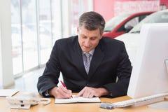 Écriture d'homme d'affaires sur le presse-papiers à son bureau Image libre de droits