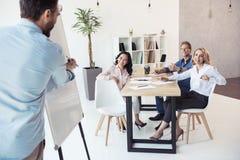 Écriture d'homme d'affaires sur le tableau blanc tandis que ses collègues s'asseyant à la table Photos stock