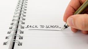 Écriture d'homme - de nouveau à l'école - dans un journal Photos stock