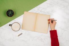 Écriture dans le carnet vide sur le fond de marbre blanc de table Photographie stock libre de droits