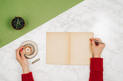 Écriture dans le carnet vide sur le fond de marbre blanc de table Photos libres de droits