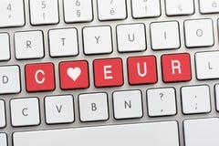Écriture de COEUR sur le clavier blanc avec un croquis de coeur Image stock