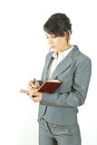Écriture de femme d'affaires dans un agenda Photographie stock libre de droits