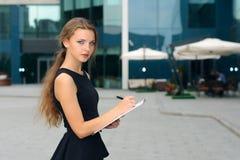 Écriture de femme d'affaires dans un dossier avec les documents et l'aw de regard image libre de droits