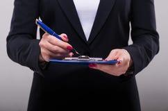 Écriture de femme d'affaires en encre sur le presse-papiers Photographie stock libre de droits