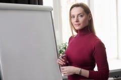 Écriture de femme d'affaires sur le flipchart tout en présentant l'exposé à Image stock