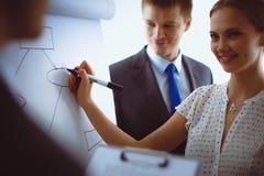 Écriture de femme d'affaires sur le flipchart tout en présentant l'exposé aux collègues dans le bureau Femme d'affaires Images stock