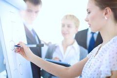 Écriture de femme d'affaires sur le flipchart tout en présentant l'exposé aux collègues dans le bureau Femme d'affaires Photos stock