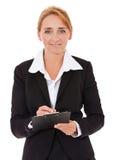 Écriture de femme d'affaires sur le presse-papiers Photo stock