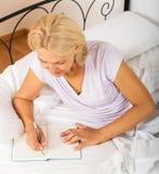 Écriture de femme dans le carnet Image stock