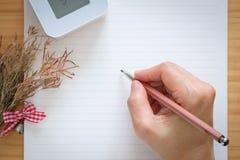 Écriture de femme sur des feuilles de papier blanc Photo stock