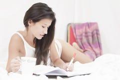Écriture de femme sur un cahier et un café potable Photos stock