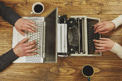 Écriture de femme sur une machine à écrire et un homme travaillant sur un ordinateur portable clos photo stock