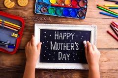 Écriture de fille avec la craie sur le petit panneau, jour de mères Photos stock