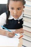 Écriture de fille d'école d'Afro-américain dans la classe image stock