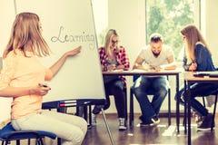 Écriture de fille d'étudiant apprenant le mot sur le tableau blanc Photos libres de droits