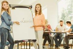 Écriture de fille d'étudiant apprenant le mot sur le tableau blanc Photographie stock libre de droits