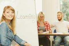 Écriture de fille d'étudiant apprenant le mot sur le tableau blanc Photos stock