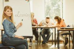Écriture de fille d'étudiant apprenant le mot sur le tableau blanc Image libre de droits