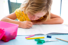 Écriture de fille d'enfant d'étudiant d'enfant avec des devoirs sur le bureau Photographie stock libre de droits