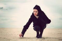 Écriture de fille dans le sable Images stock