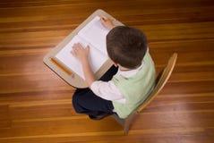 Écriture de garçon au bureau d'école Photos stock