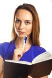 Écriture de jeune femme dans son organisateur Photos stock