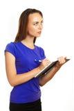 Écriture de jeune femme dans son organisateur Image stock