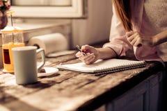 Écriture de jeune fille dans le carnet dans la cuisine Photos libres de droits