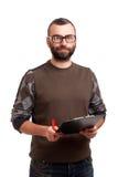 Écriture de jeune homme sur un presse-papiers Image stock