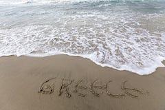 Écriture de la Grèce sur le sable avec de l'eau venant pour l'effacer Photos stock