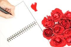 Écriture de la main des femmes sur le carnet avec les roses rouges Photos stock