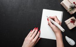 Écriture de lettre de Noël sur le livre blanc sur le fond noir avec des boîte-cadeau Concept de Noël et de nouvelle année, vue su Images stock