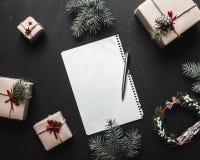 Écriture de lettre de Noël sur le livre blanc sur le fond noir avec des cadeaux Image stock