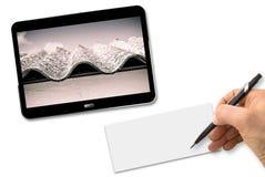 Écriture de main avec un crayon sur une page blanche au-dessus d'un bureau blanc avec un comprimé numérique montrant un toit dang image stock
