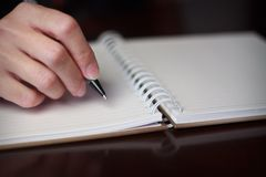 Écriture de main avec un stylo dans un carnet Photo libre de droits