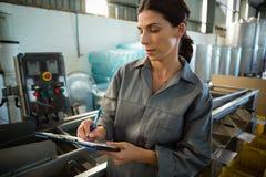 Écriture de main-d'œuvre féminine sur le presse-papiers dans l'usine olive photo libre de droits