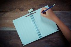 Écriture de main dans le carnet ouvert sur la table Photographie stock libre de droits