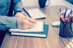Écriture de main dans le carnet sur la table en bois Photo stock