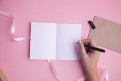 Écriture de main de femmes sur le livre blanc Photographie stock libre de droits