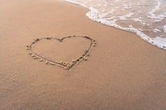 Écriture de main de forme de coeur sur la plage sablonneuse Images stock