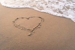 Écriture de main de forme de coeur sur la plage sablonneuse Photo stock