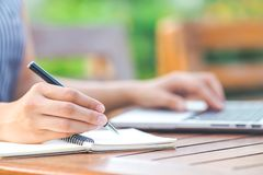 Écriture de main de femme d'affaires sur le bloc-notes avec un stylo et une La de fonctionnement Photos stock