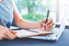 Écriture de main de femme sur le bloc-notes avec un stylo dans le bureau Photos stock