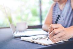 Écriture de main de femme sur le bloc-notes avec un stylo dans le bureau Photo stock