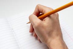 Écriture de main sur la feuille rayée blanche de carnet avec un crayon jaune photographie stock libre de droits