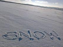 Écriture de neige sur le champ Photos stock